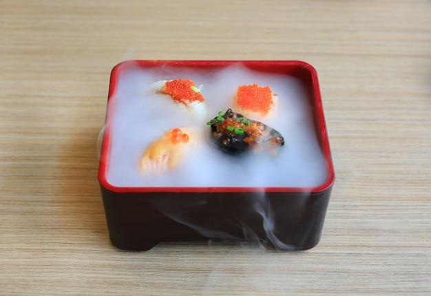 O grupo do sushi de nami seriu com frio fumado na tabela de madeira. comida japonesa tradicional.
