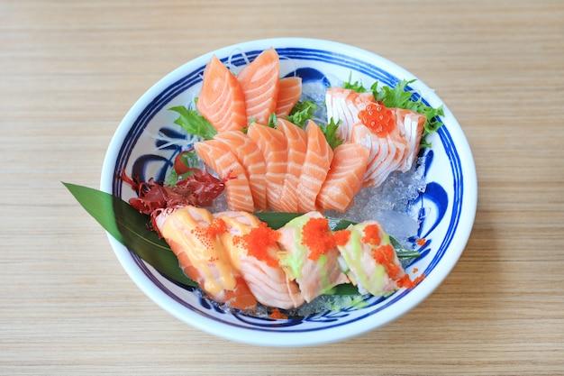 O grupo do sushi do sashimi serviu no gelo contra a tabela de madeira. comida japonesa.