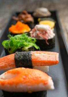 O grupo do sushi e os rolos de sushi serviram na tabela de madeira.