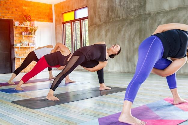 O grupo fêmea asiático da aptidão que faz aquece a pose da ioga na fileira na classe da ioga. foco seletivo