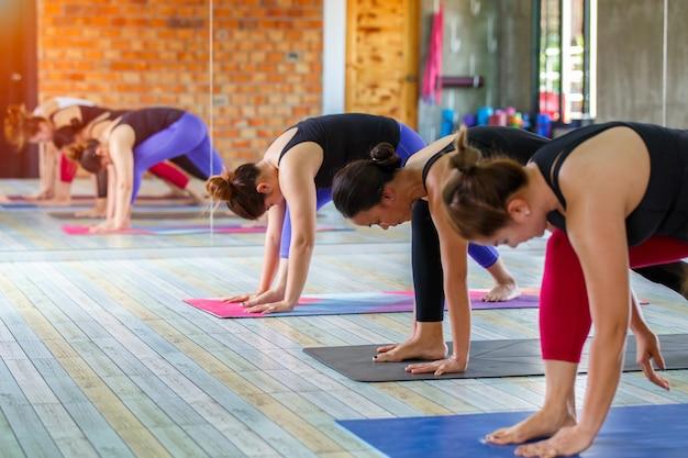 O grupo fêmea asiático da aptidão que faz aquece a pose da ioga na fileira na classe da ioga.