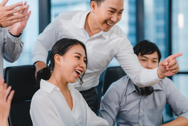 O grupo milenar de jovens empresários ásia empresário e empresária comemoram dando cinco depois de lidar sentindo-se feliz e assinando contrato ou acordo na sala de reuniões no pequeno escritório moderno.
