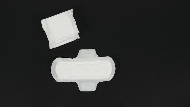 O guardanapo sanitário com asa é isolado no fundo preto. sem pessoas