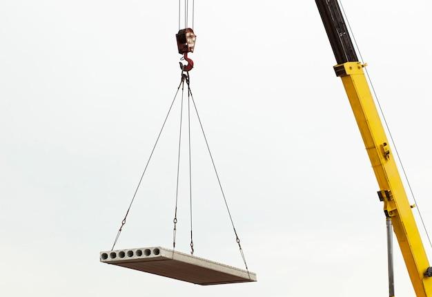 O guindaste de construção levantando a placa de concreto