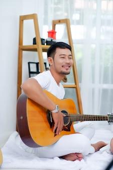 O guitarrista, o homem sentado sorrindo feliz.