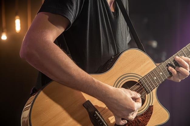 O guitarrista toca violão em show com uma palheta em um fundo preto desfocado close-up.