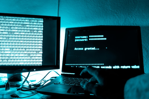 O hacker imprime um código em um teclado de laptop para invadir um sistema de organização secreta.