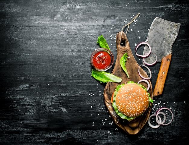 O hambúrguer e os ingredientes frescos no antigo tabuleiro. em um quadro negro. vista do topo.