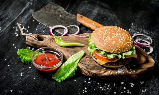 O hambúrguer e os ingredientes frescos no antigo tabuleiro. em um quadro negro.