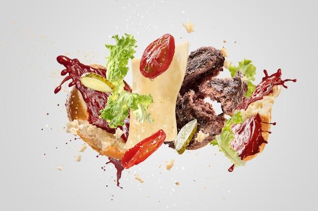 O hambúrguer está quebrando isolado no fundo branco. saborosa e deliciosa combinação de pãezinhos, tomates, ketchup, pepinos, saladas, queijos e costeleta de carne de porco. alimentação gourmet e tradicional, nutrição.