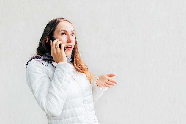 O headshot do retrato da mulher caucasiano nova gesticula entusiasticamente discutindo no telefone móvel.