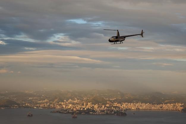 O helicóptero voa na cidade do rio de janeiro, brasil.