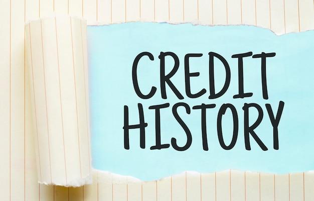 O histórico de crédito do texto aparecendo atrás de um papel branco rasgado