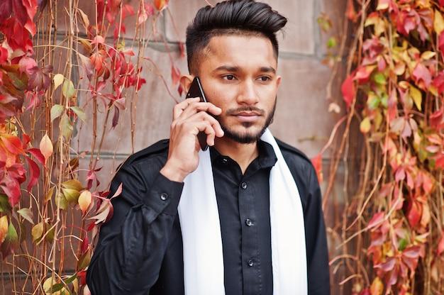 O homem à moda indiano na roupa tradicional preta com lenço branco levantou exterior contra a parede vermelha das folhas que fala no telefone celular.