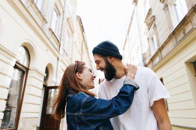 O homem abraça a mulher de trás de pé com ela na rua