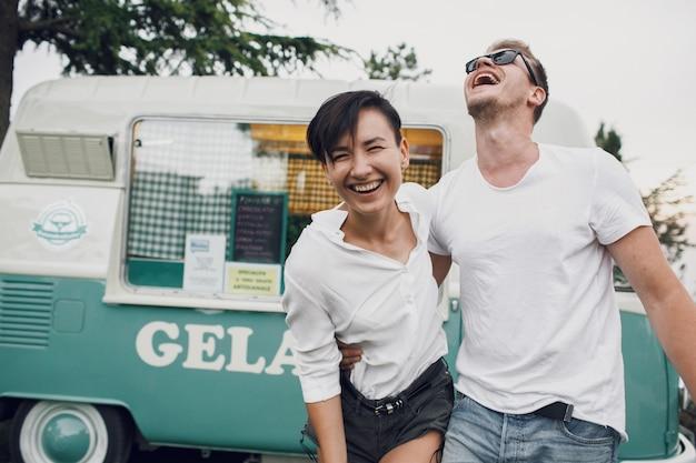 O homem abraça e beija mulher deslumbrante de pé diante de um ônibus