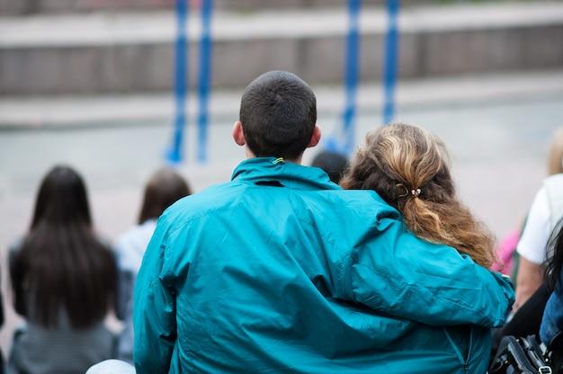 O homem abraça os ombros de uma mulher. vista traseira.