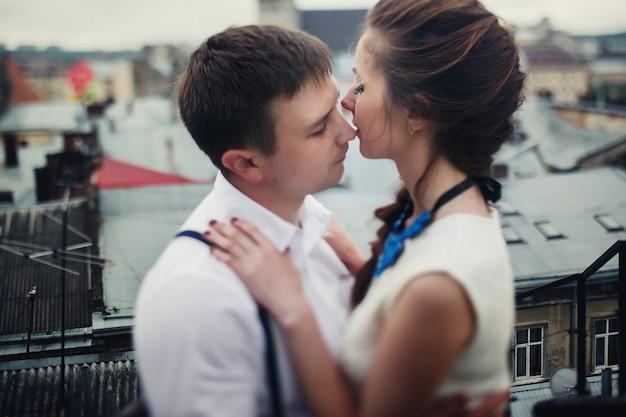 O homem abraça uma linda mulher bonita e a beija na cobertura