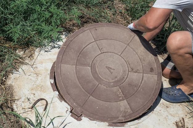 O homem abre a tampa do poço de água do poço. verificar e consertar a medição de água.
