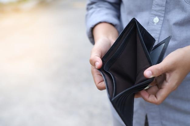 O homem abre uma carteira vazia por causa do impacto da crise econômica.