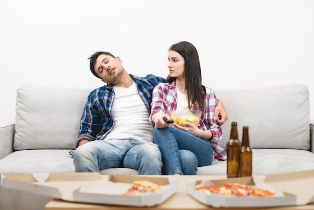 O homem adormecido e uma mulher sentados no sofá no fundo da parede branca