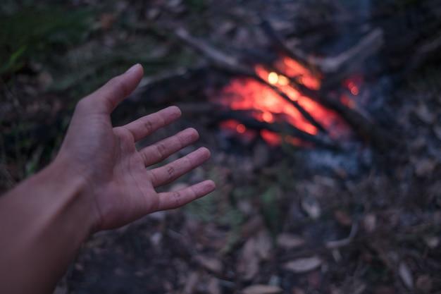 O homem adulto aquece as mãos ao redor da fogueira na floresta.