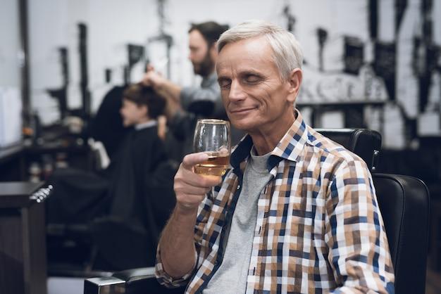 O homem adulto é cortado na barbearia.