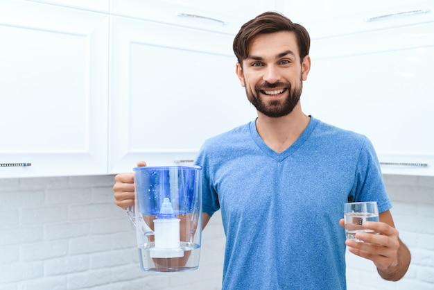 O homem adulto é derrama a água do filtro de água no vidro.