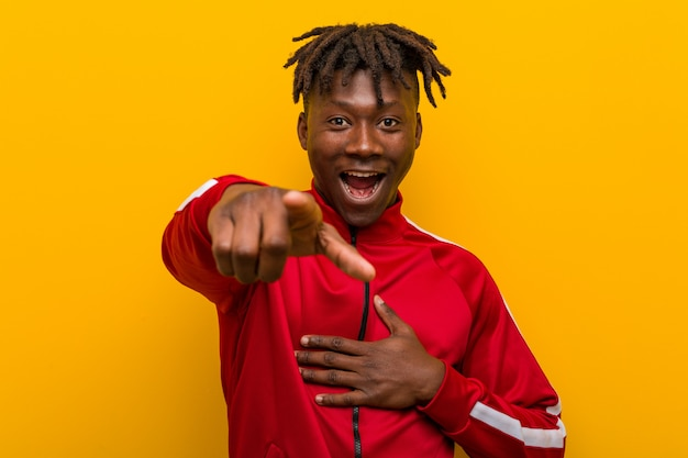 O homem africano da aptidão nova aponta com o dedo do polegar afastado, rindo e despreocupado.