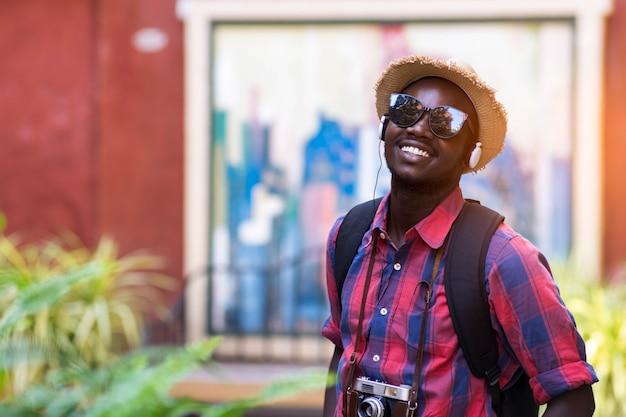 O homem africano do turista sente feliz com lugar do curso na cidade do cenário.