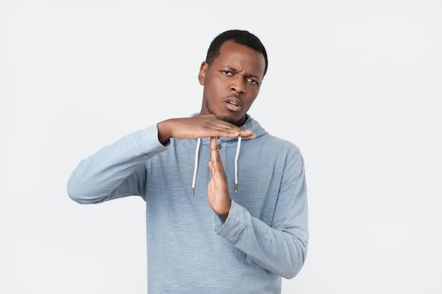 O homem africano novo que mostra o tempo para fora entrega o gesto isolado.