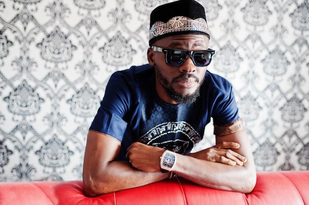 O homem africano rico na roupa tradicional à moda e o chapéu nos vidros levantaram na sala contra o fundo do vintage, perto do sofá-cama de couro vermelho.