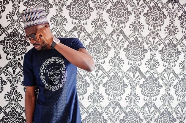 O homem africano rico na roupa tradicional à moda e o chapéu nos vidros levantaram no estúdio contra o fundo do vintage.
