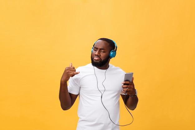 O homem afro-americano com fones de ouvido escuta e dança com música. isolado em fundo amarelo