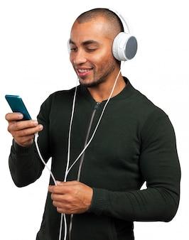 O homem afro-americano considerável está escutando a música