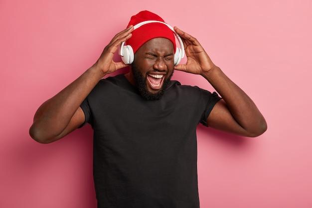 O homem afro-americano curte music player ou gravador de áudio, mantém as mãos nos fones de ouvido, se diverte enquanto ouve músicas populares, isoladas na parede rosa.
