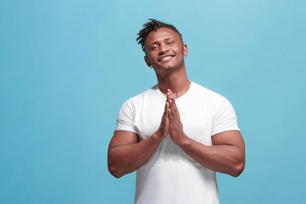 O homem afro-americano de negócios feliz em pé e sorrindo contra a parede azul