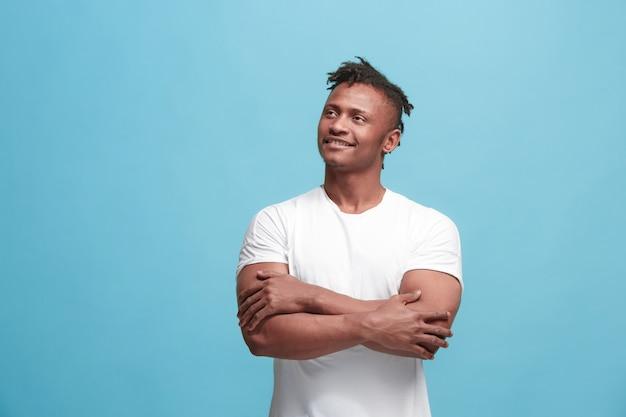 O homem afro-americano de negócios feliz em pé e sorrindo contra o azul.