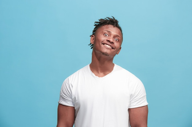 O homem afro-americano de olhos vesgos com expressão estranha isolada no azul