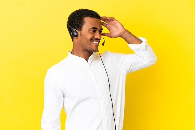 O homem afro-americano do operador de telemarketing que trabalha com um fone de ouvido sobre um fundo amarelo isolado percebeu algo e pretende encontrar a solução