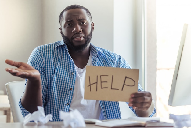 O homem afro-americano em roupas casuais está pedindo ajuda.