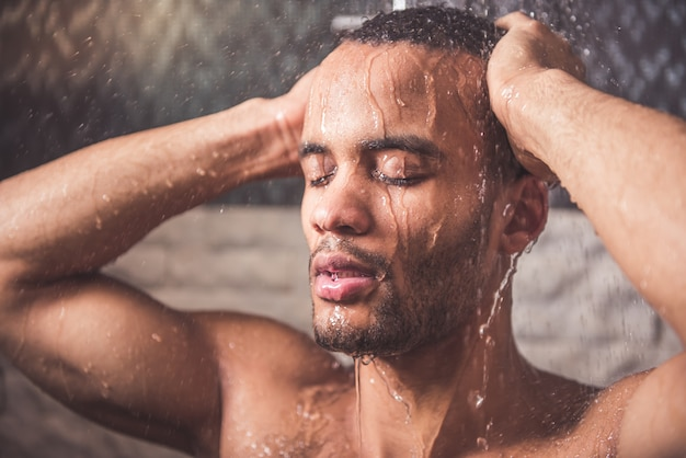 O homem afro-americano está tomando o chuveiro no banheiro.