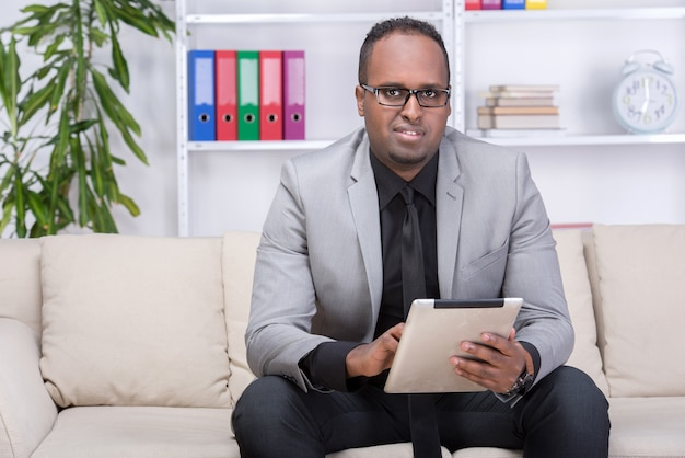 O homem afro-americano está usando a tabuleta digital em casa.