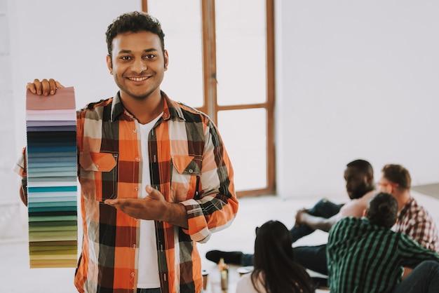 O homem afro-americano feliz está mostrando a paleta de cores.