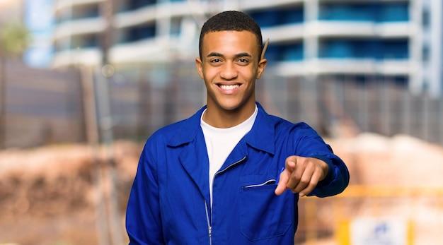 O homem afro-americano novo do trabalhador aponta o dedo em você com uma expressão confiável em um canteiro de obras