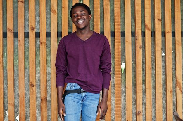 O homem afro-americano novo na ligação em ponte violeta levantou contra a parede de madeira.
