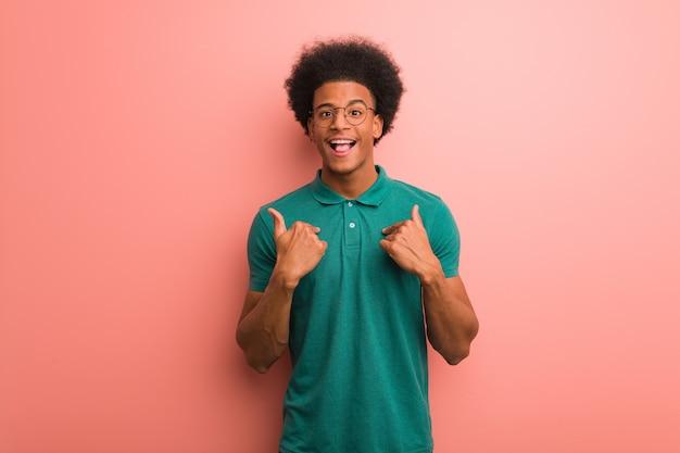 O homem afro-americano novo sobre uma parede cor-de-rosa surpreendeu, sente bem sucedido e próspero