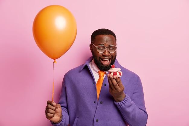 O homem afro solitário olha insatisfeito para um pequeno bolinho doce, comemora o evento festivo sozinho, segura um balão de ar