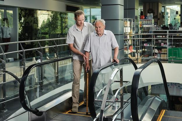 O homem ajuda o velho a descer da escada rolante
