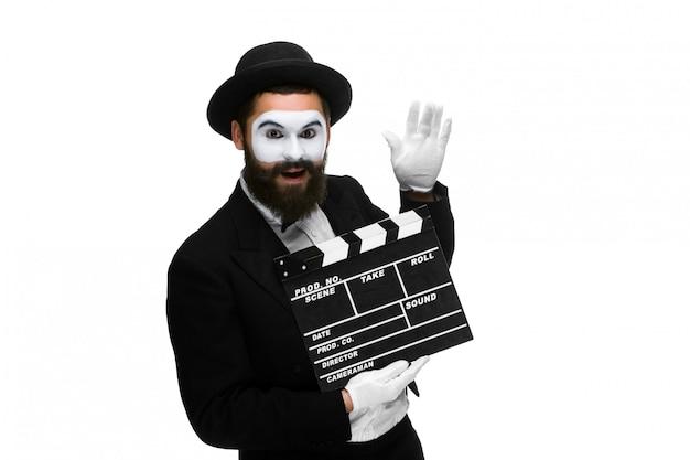 O homem alegre na imagem mimica com placa de filme
